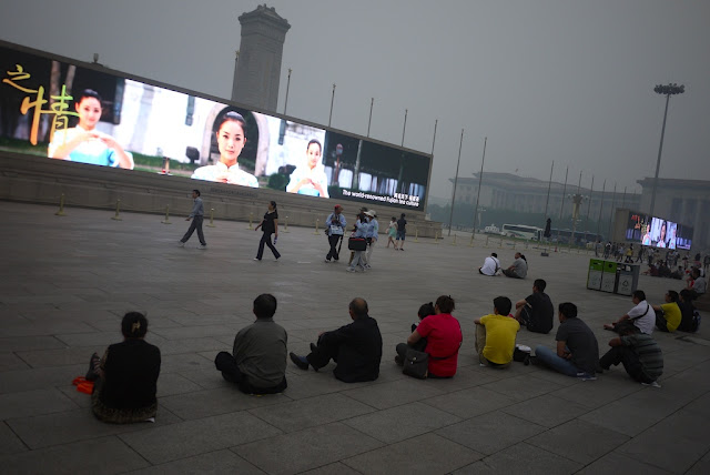 people watching a large video display at Tiananmen Square