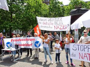 Friedensbewegte mit Fahnen und Transparenten: »Warum unterstützt die deutsche Politik ukrainische Nazis?«, »Friedensforum Düsseldorf«, »Stoppt die NATO«.