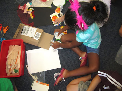Child works with many different types of materials to construct a container for her favorite food.