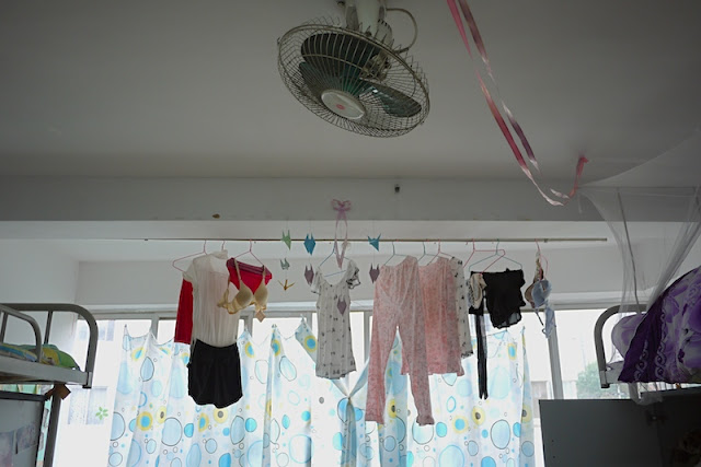 fan and hanging clothes inside a female dormitory room at Central South University of Forestry and Technology in Changsha, China.