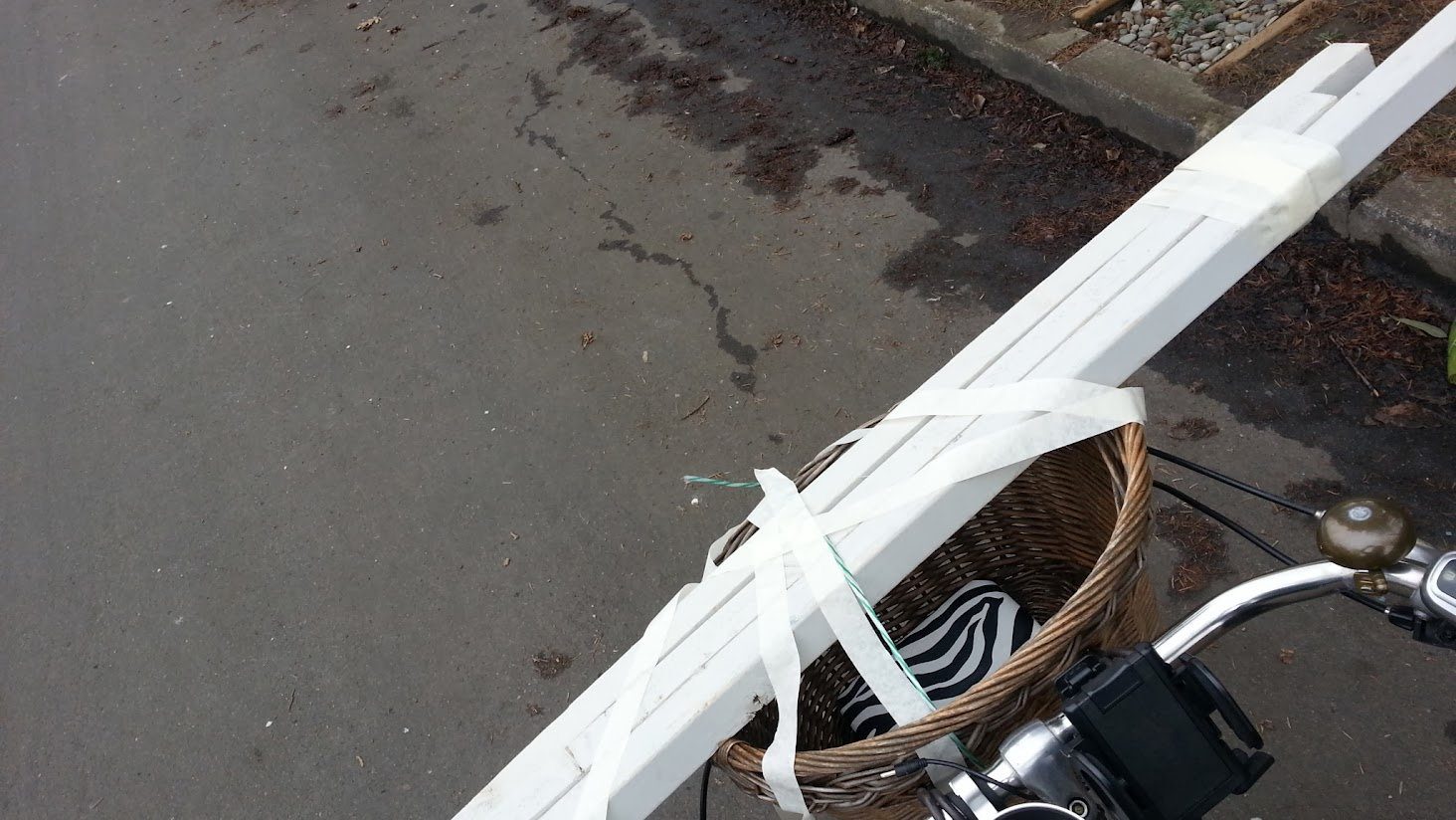 White two by two lumber taped and tied across the basket on Eleanor O the Dutch Bike's handlebars