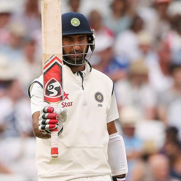 India's Cheteshwar Pujara celebrates reaching a half century (50 runs) during the fourth day of the first cricket Test match between England and India at Trent Bridge in Nottingham, central England on July 12, 2014.