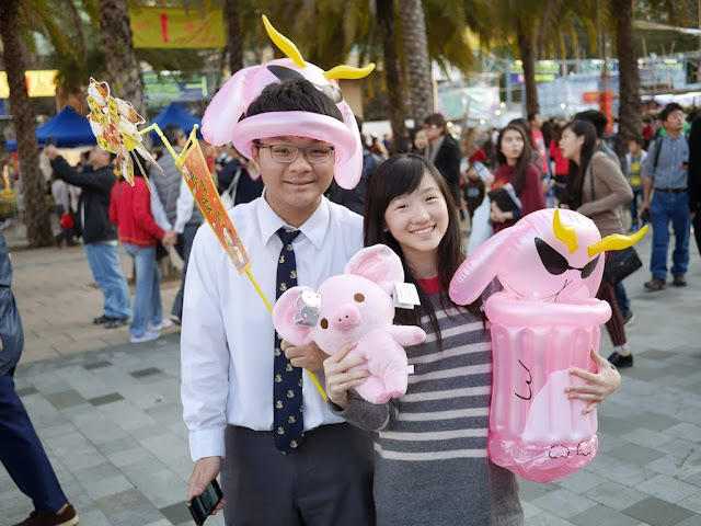 high school boy and girl holding and wearing pink inflatable items and a pink stuffed animal