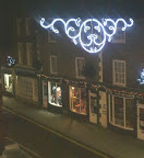 Looking at xmas lights at night, with residential dwellings above all the shops on the street