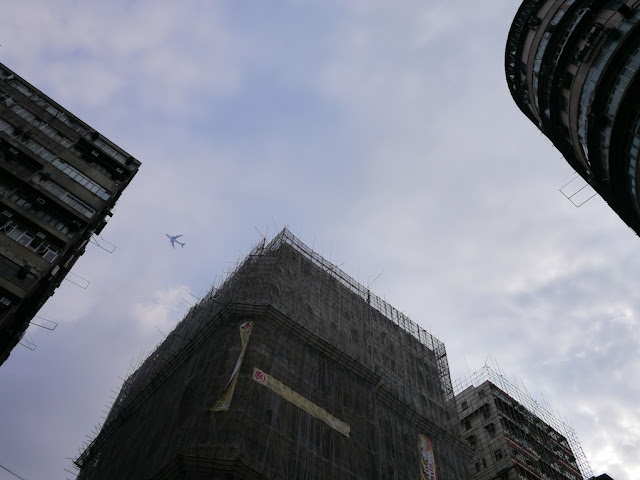 view between two buildings of a plane flying above