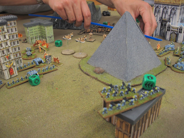 Wolves clash with Guard amidst the ruins of a grey pyramid.