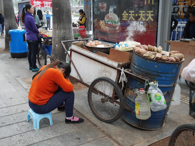Food vendor resting in Zhuhai near an advertisement for McDonald's