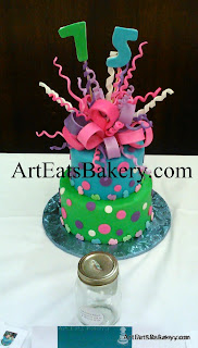 Two tier custom creative blue, pink, purple, and green March of Dimes 75th birthday fund raiser cake with polka dots, baby feet and edible bow topper