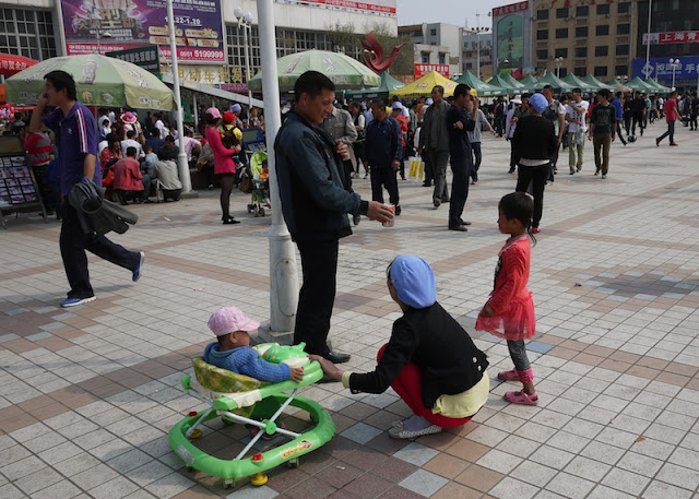 man handing a canned drink to a little girl at Nanmen Square in Yinchuan, Ningxia, China