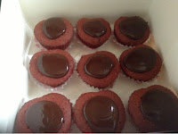 box of red velvet cupcakes with chocolate topping