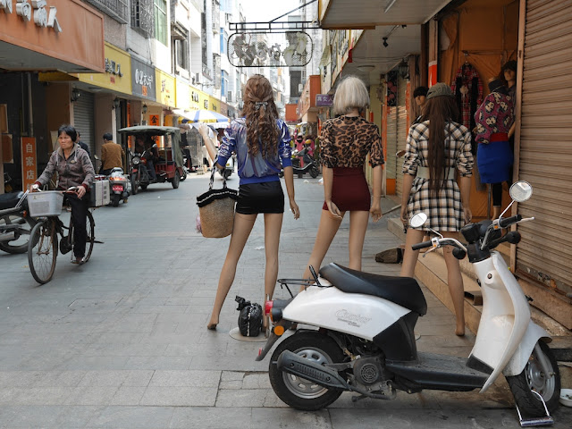 mannequins and woman on a bicycle in Yangjiang, China