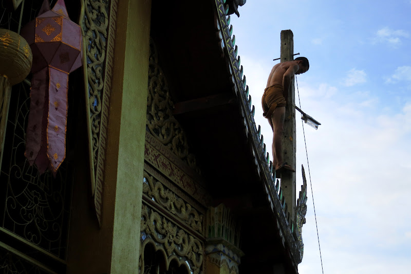 Monk climbing a pole