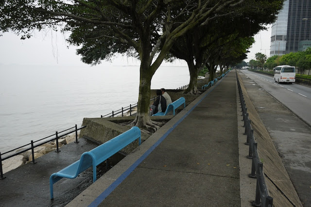 waterfront in Macau with 2 people sitting on a bench and an empty walkway