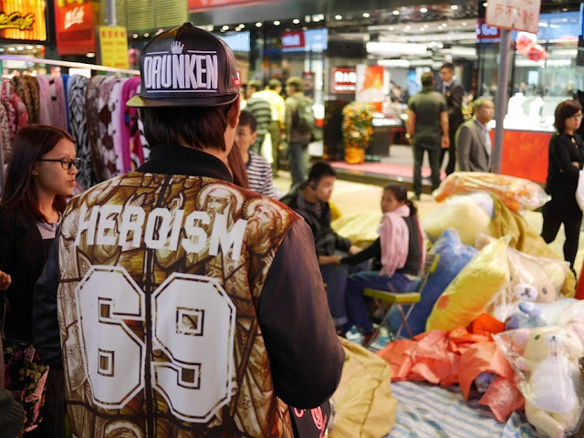 "young man wear at hat with the word ""DRUNKEN"" on it and a coat with ""HEROISM 69"" at Sai Yeung Choi Street South"