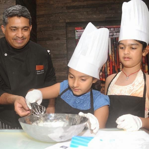Girish Krishnan , Executive Chef JW Marriott New Delhi Aerocity guiding the kids during the baking session hosted by Ritu Beri in Delhi.