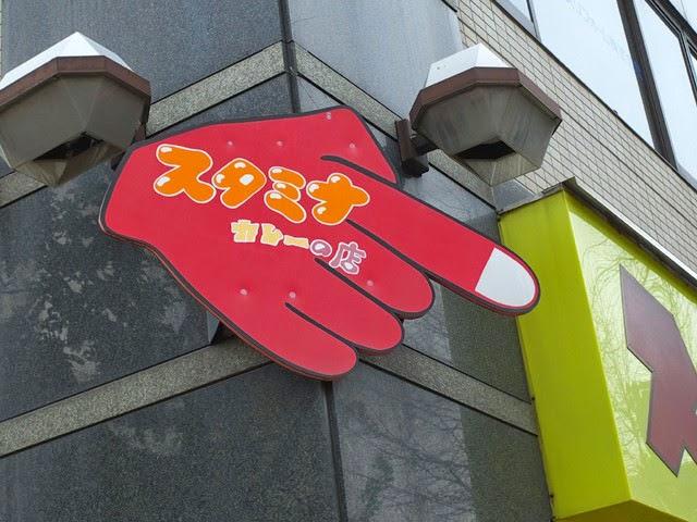 手の形ので指さされた「スタミナカレーの店」の案内