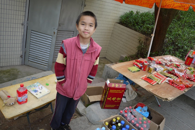 Boy standing near drinks and packaged food for sale at Jingshan Park in Zhuhai