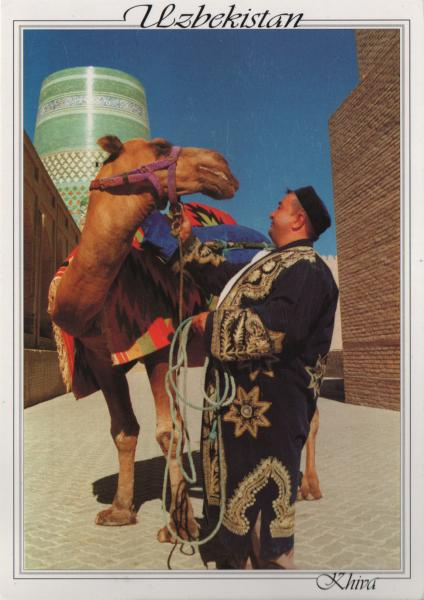 man holding camel in front of brick walls