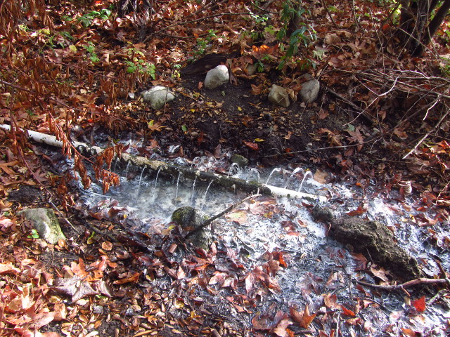 water flowing from holed pipe