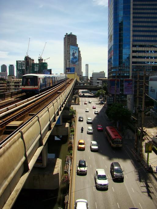 Tren sobrevolando autopista por encima de calle puesta encima de un río
