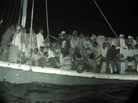 Flüchtende nachts in überfülltem Boot.
