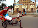 """And most """"pousse-pousse"""" drivers RUN the whole time they transport people, only slowing to a walk as they trudge up steep hills. This guy was running by in front of Antsirabe's big Catholic church, with a passenger and her luggage."""
