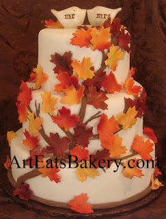 Romantic wedding cake with unique creative orange, red, yellow and brown edible fall leaves design and bird toppers