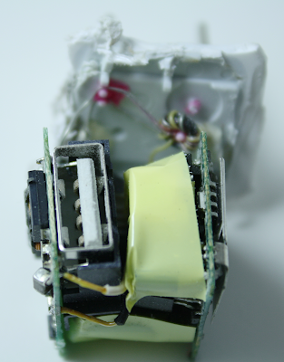 Inside the Apple iPhone charger. The two circuit boards and the USB jack are visible. The AC connection is at the back.