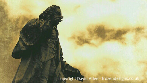 A Sepia photograph of Isaac Watts statue in southampton against an overcast sky