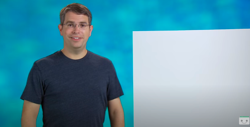 A man with eyeglasses and a dark blue shirt standing on a light-blue background.