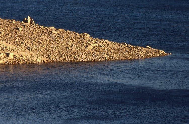 Pormenor de uma ponta de terra nas águas da albufeira