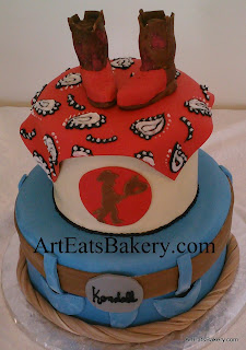 Two tier cowboy unique creative kid's cake design with blue jeans, belt, bandana and handmade edible red and brown boots topper