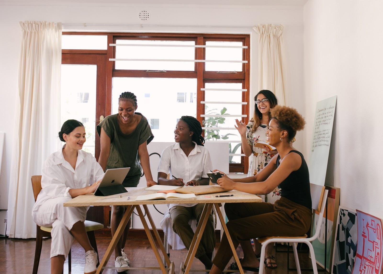 Várias mulheres conversando em uma mesa.