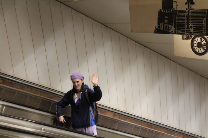 woman waves from the up escalator