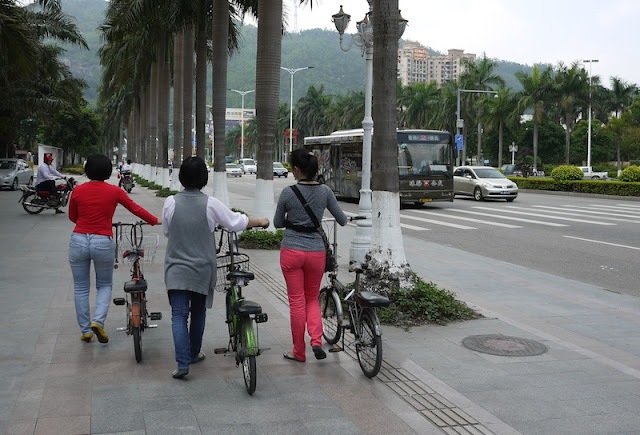 Three women pushing bicycles on a sidewalk in Zhuhai, China.