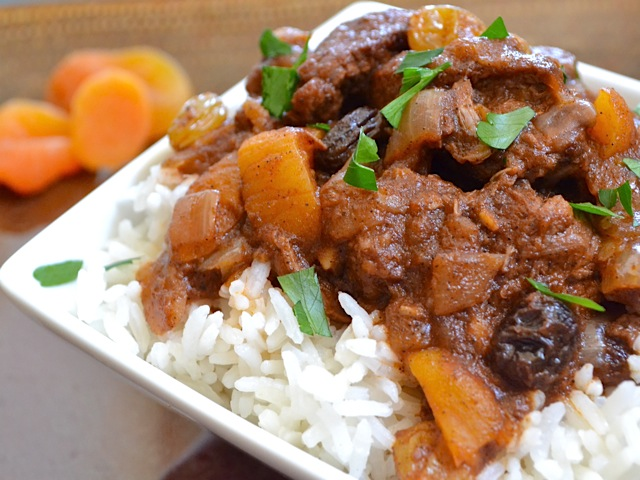 moroccan beef stew on a bed of white rice plated on a white plate