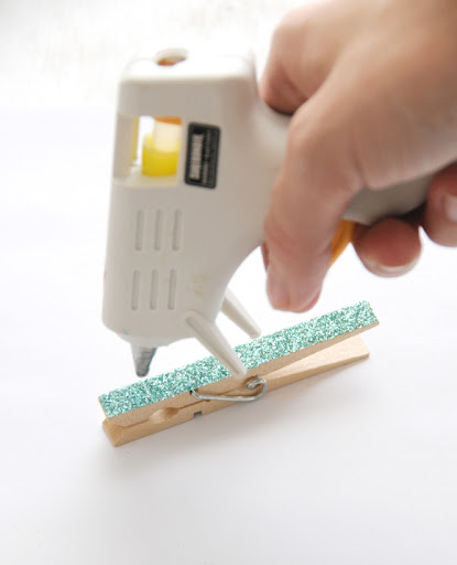 Carefully apply a small dot of hot glue onto your clothespin where you'd like your decorative piece to sit. Easy peasy!