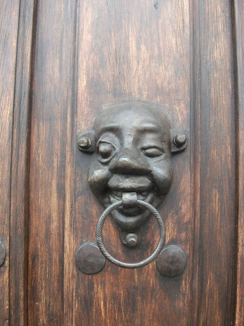 Latch made out of wrought iron shaped like a smiling face with a big nose and one popping eye
