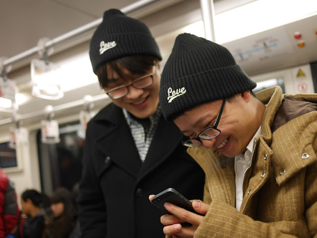 "two smiling young men wearing ""Love"" winter hats and looking at a mobile phone while riding the subway"
