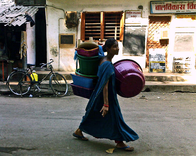 young woman carrying plastic buckets for sale