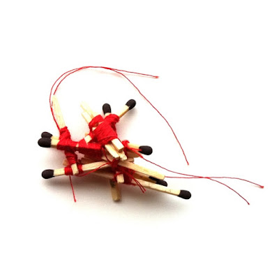 A bundle of matches which have been bound together in a haphazard manner with red thread.