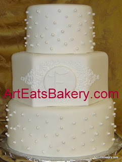 Three tier custom designed unique white fondant wedding cake with sugar pearls, monogram, and curlicues