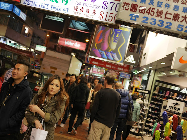 couple walking on a busy sidewalk in Mong Kok