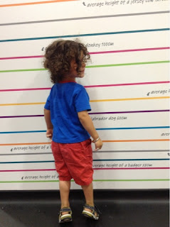 toddler standing next to a height chart in Kiddicare