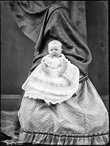 Mãe coberta por uma pano, segurando seu bebê no século XIX