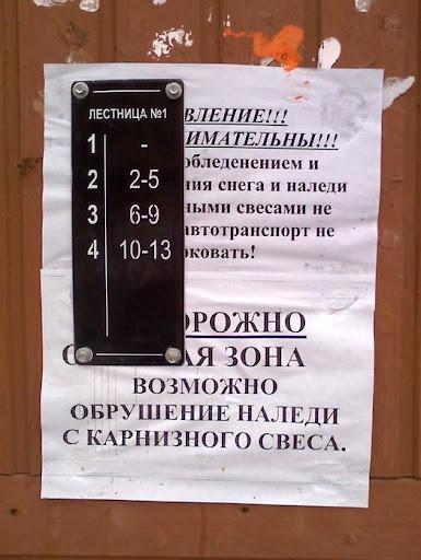 Табличка с номерами квартир прибита поверх бумажных объявлений