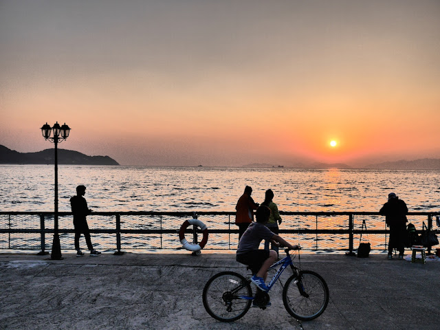 people looking at the sea and a biker riding by as the sun sets at the Cyberport Waterfront Park in Hong Kong