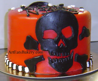 Red fondant unique birthday cake design with black scull and crossbones and mini black and white sculls