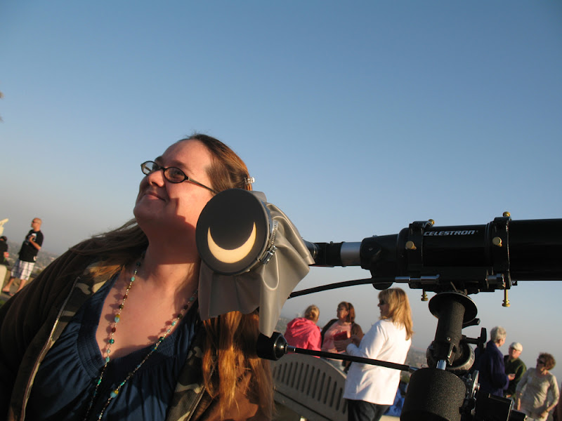 Young woman poses next to grinning solar eclipse of May 20, 2012