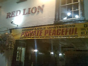 Yellow theatre banner over pub archway proclaiming 'Private Peaceful' as next show